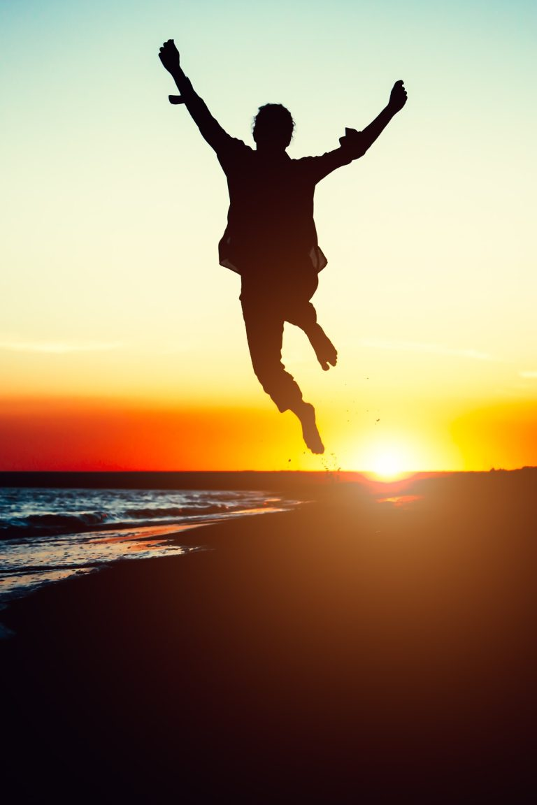 Silhouette young woman jumping with hands up on the beach at the